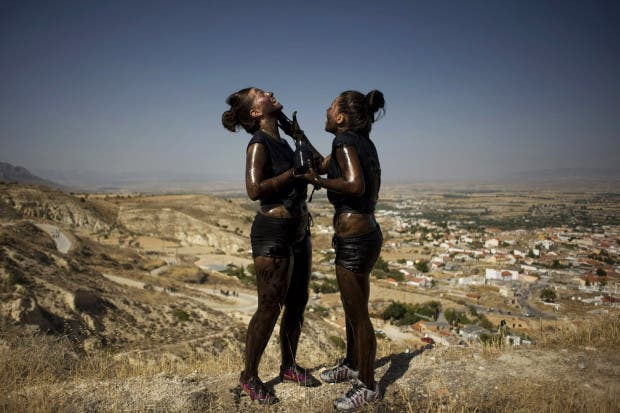 Image: Youths cover each other in black grease for Cascamorras