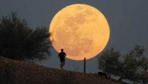 "A runner makes his way along a trail on a butte in front of the ""super Moon""  at Papago Park in Phoenix"