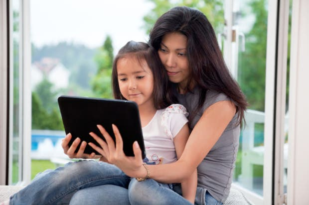 Mother and girl holding E-book reader at home