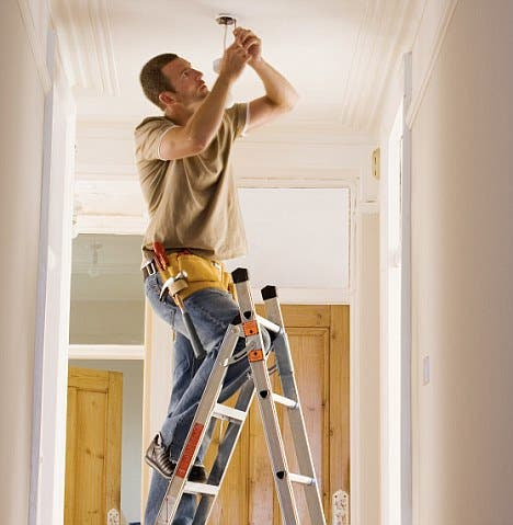 Man with toolbelt doing DIY at home, standing on step ladder, fixing light fixture in ceiling