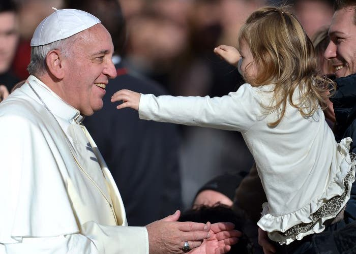 Pope Francis is about to hug a young girl during his general audience in St Peter's square at the Vatican on December 4, 2013. AFP PHOTO / FILIPPO MONTEFORTE