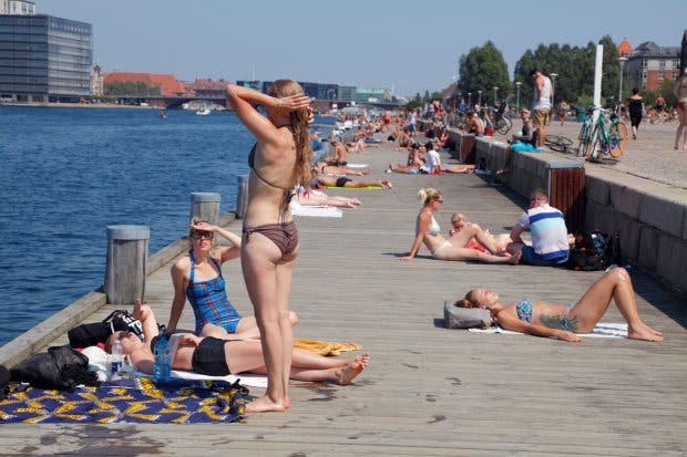 CTM2AN Young people sunbathing and swimming from the Islands Brygge quay in the harbour of Copenhagen, Denmark, on a hot summer day.