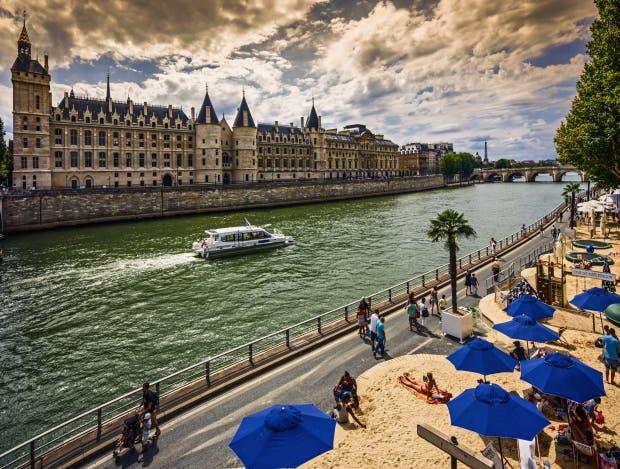 People enjoy the sun during 'Paris-Plages' on quays of Seine river, 'Conciergerie', 'Pont Neuf' bridge, Eiffel Tower, Paris, France