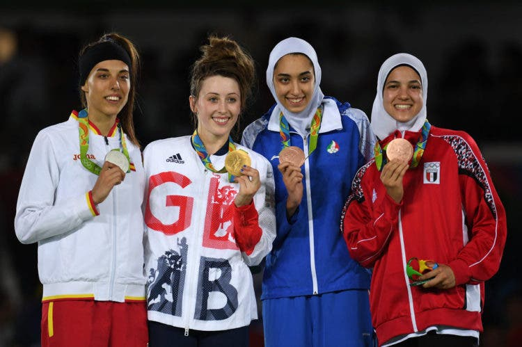 RIO DE JANEIRO, BRAZIL - AUGUST 18: Silver medalist Eva Calvo Gomez of Spain, gold medalist, Jade Jones of Great Britain and bronze medalists Kimia Alizadeh Zenoorin and Hedaya Wahba of Egypt celebrate on the podium after the Women's -57kg Taekwondo contests at the Carioca Arena on Day 13 of the 2016 Rio Olympic Games on August 18, 2016 in Rio de Janeiro, Brazil. (Photo by Laurence Griffiths/Getty Images)