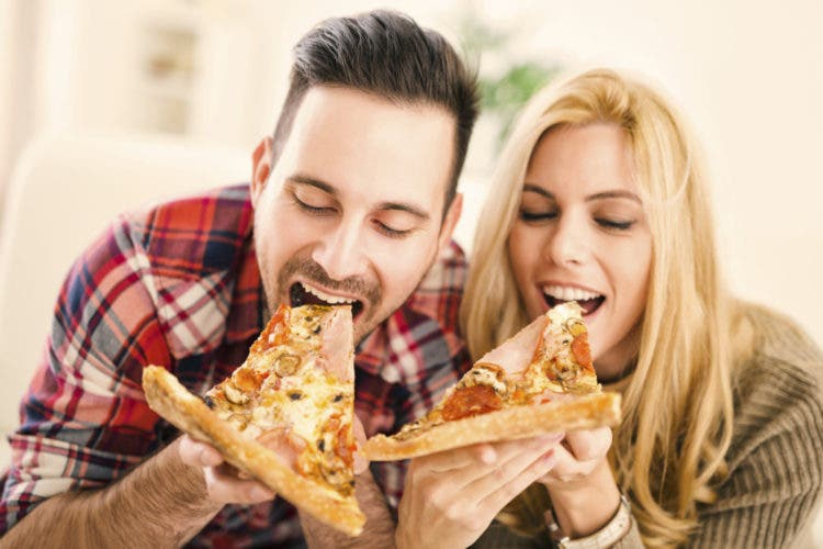 Portrait of an happy couple.They are laughing and eating pizza and having a great time.
