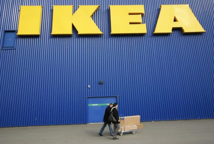 REFILE - CORRECTING MONTH IN SECOND SENTENCE People push a shopping cart past a warehouse of the Swedish furniture maker IKEA in Bordeaux, southwestern France, in this February 13, 2010 file photograph. Sweden's IKEA, the world's largest furniture maker, is set to enter the consumer electronics market with products developed in co-operation with China-based TCL Multimedia, IKEA officials said on April 17, 2012. IKEA, known the world over for low-price, self-assembly flat-packed furniture, plans to launch a line of furniture with integrated connected television and sound systems in five European cities in June, throughout seven European countries this autumn, and in its remaining markets in the summer of 2013. REUTERS/Olivier Pon/Files (FRANCE - Tags: BUSINESS)