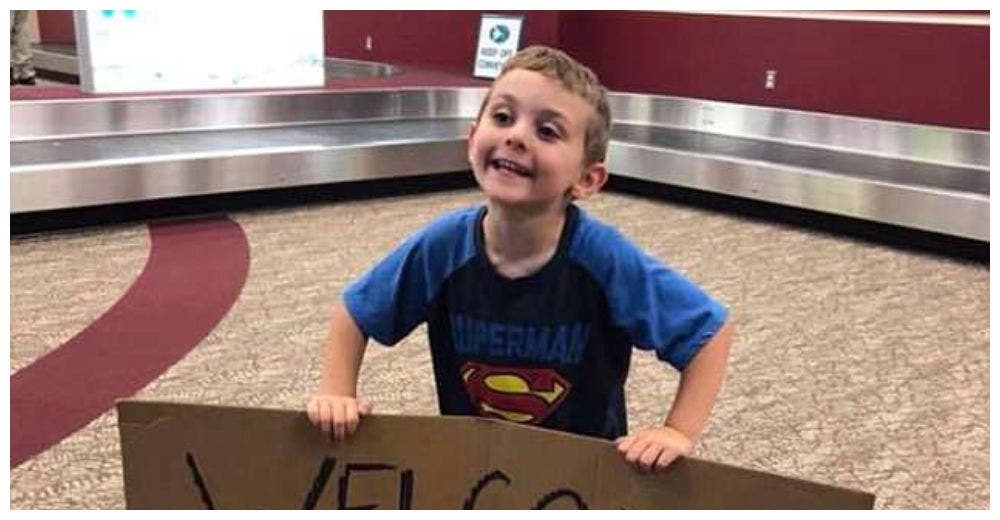 Un niño de 4 años espera a su madre en el aeropuerto con un vergonzoso cartel de bienvenida
