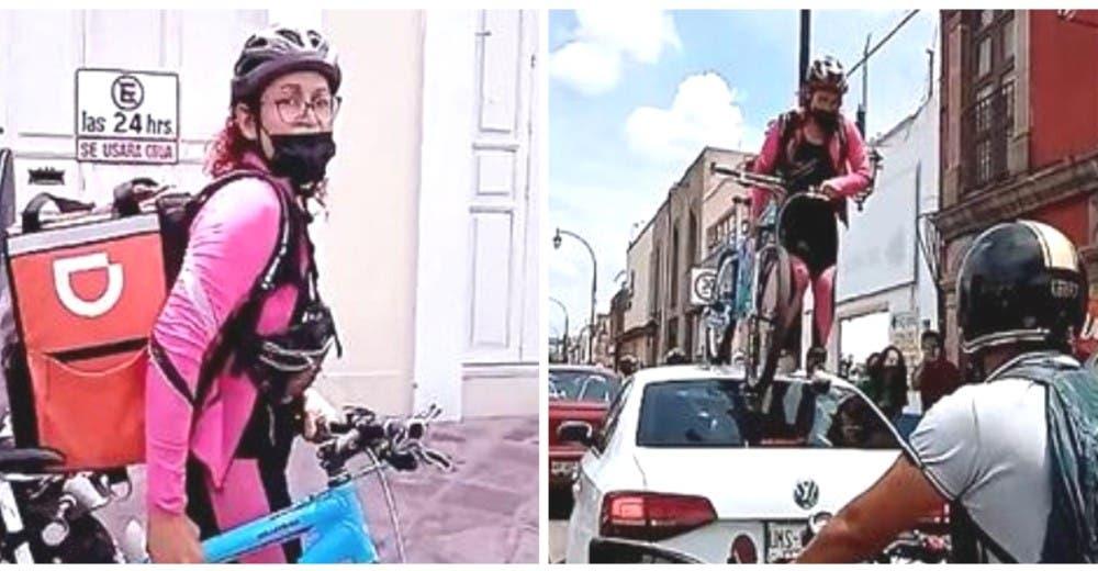 Una ciclista pasa con su bicicleta sobre un auto aparcado en la ciclovía