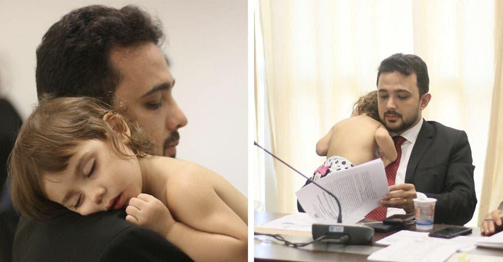 Un padre sostiene amorosamente a su hija en brazos durante una reunión de trabajo